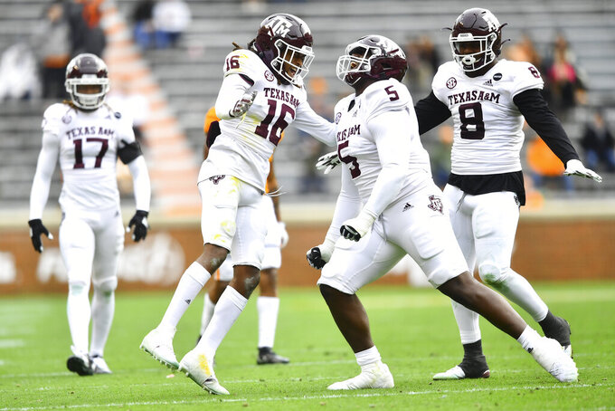 Texas A&M defensive back Brian George (16), and defensive linemen Bobby Brown III and DeMarvin Leal (8) celebrate against Tennessee during an NCAA college football game in Neyland Stadium in Knoxville, Tenn., Saturday, Dec. 19, 2020. (Brianna Paciorka/Knoxville News Sentinel via AP, Pool)