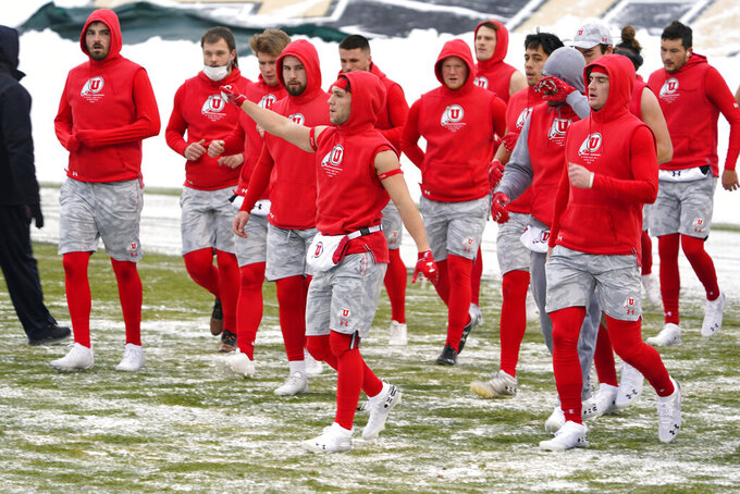 Utah wide receiver Britain Covey, center, raises his arm as he warms up with teammates in sub-freezing temperatures and light snow before the first half of an NCAA college football game Saturday, Dec. 12, 2020, in Boulder, Colo. (AP Photo/David Zalubowski)
