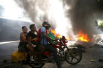 A moto-taxi driver takes two women around a burning barricade set up by people protesting fuel shortages in Petion-ville, Haiti, Sunday, Sept. 15, 2019. Gas stations have been reducing their operating hours over the past weeks, and the majority were closed this week. (AP Photo/Dieu Nalio Chery)