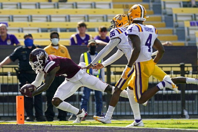 Mississippi State wide receiver Tyrell Shavers (9) dives over the goal line ahead of LSU running back Keenen Dunn (26) and safety Todd Harris Jr. (4) on a touchdown reception in the first half an NCAA college football game in Baton Rouge, La., Saturday, Sept. 26, 2020. (AP Photo/Gerald Herbert)