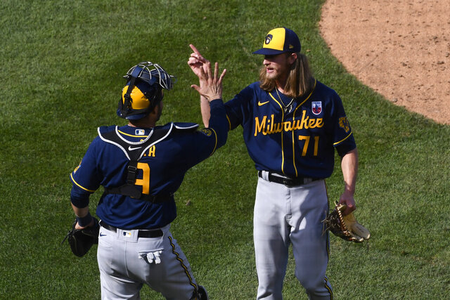Milwaukee Brewers relief pitcher Josh Hader signals with catcher Manny Pina (9) after a baseball game against the Chicago Cubs, Sunday, Aug. 16, 2020, in Chicago (AP Photo/Matt Marton)