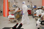 Medical staff attend to patients in the emergency room, turned into a CODIV-19 unit due the high number of cases, at the Bagdasar-Arseni hospital in Bucharest, Romania, Tuesday, Oct. 12, 2021. Romania reported on Tuesday nearly 17,000 new COVID-19 infections and 442 deaths, the highest number of coronavirus infections and deaths in a day since the pandemic started, as the nation's health care systemstruggles to cope with an acute surge of new cases.(AP Photo/Andreea Alexandru)