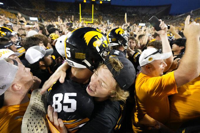 A fan hugs Iowa defensive lineman Logan Lee (85) on the field after Iowa beat Penn State 23-20, in an NCAA college football game, Saturday, Oct. 9, 2021, in Iowa City, Iowa. (AP Photo/Matthew Putney)