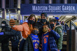 The Quershif family take a selfie outside Madison Square Garden before an NBA basketball game between the New York Knicks and the Golden State Warriors in New York on Tuesday, Feb. 23, 2021. A limited number of fans was allowed to attend. (AP Photo/Brittainy Newman)
