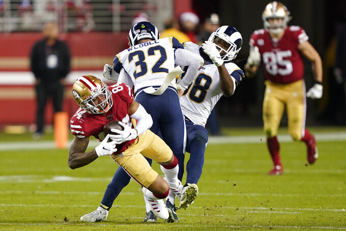 San Francisco 49ers wide receiver Kendrick Bourne (84) catches a pass next to Los Angeles Rams' Eric Weddle (32) and Cory Littleton during the second half of an NFL football game in Santa Clara, Calif., Saturday, Dec. 21, 2019. (AP Photo/Tony Avelar)