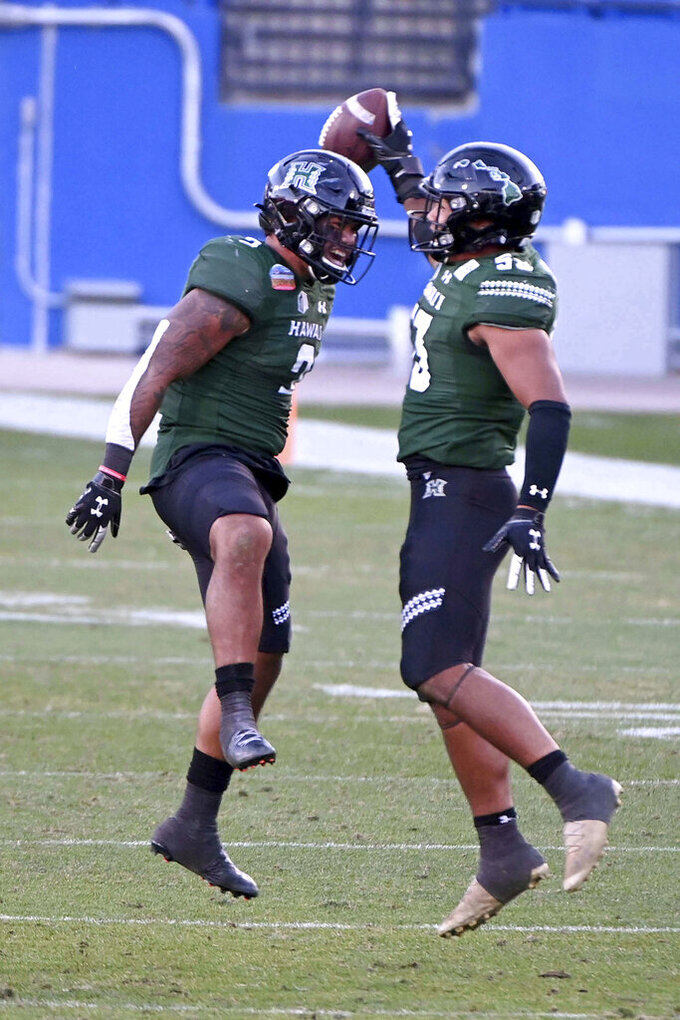 Hawaii defensive back Khoury Bethley (5) and linebacker Darius Muasau (53) celebrate Muasau's interception in the third quarter of the New Mexico Bowl NCAA college football game against Houston in Frisco, Texas, Thursday, Dec. 24, 2020. (AP Photo/Matt Strasen)