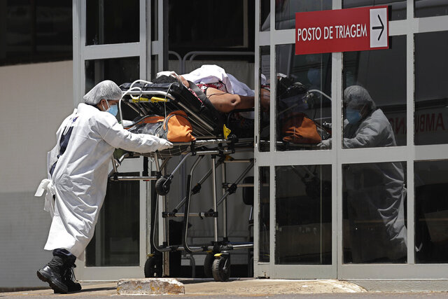 Health workers push a patient suspected of having COVID-19 into the HRAN Hospital in Brasilia, Brazil, Thursday, Jan. 7, 2021.  (AP Photo/Eraldo Peres)