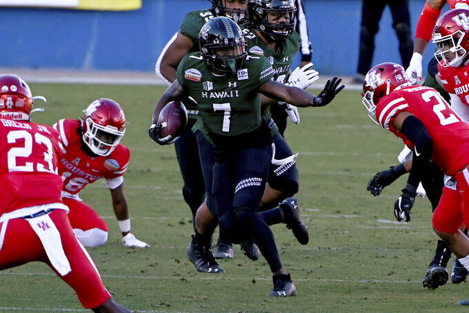 Hawaii running back Calvin Turner (7) looks for running room through the Houston defense during the second quarter of the New Mexico Bowl NCAA college football game in Frisco, Texas, Thursday, Dec. 24, 2020. (AP Photo/Matt Strasen)