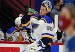 St. Louis Blues goaltender Jordan Binnington sprays water from his bottle during a timeout in the second period of the team's NHL hockey game against the Colorado Avalanche on Wednesday, Jan. 13, 2021, in Denver. (AP Photo/David Zalubowski)