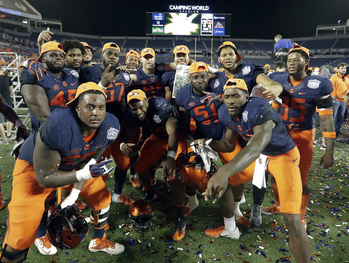 Syracuse players celebrate after defeating West Virginia in the Camping World Bowl NCAA college football game Friday, Dec. 28, 2018, in Orlando, Fla. (AP Photo/John Raoux)