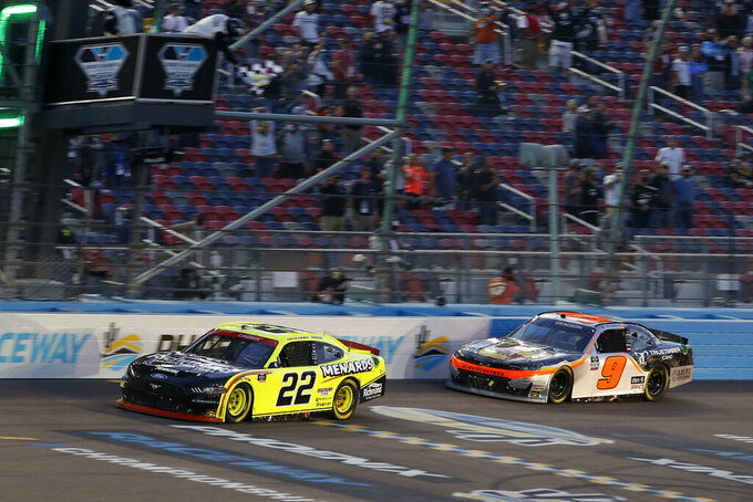 Austin Cindric (22) crosses the finish line ahead of Noah Gragson (9) to win a NASCAR Xfinity Series auto race and the season championship at Phoenix Raceway, Saturday, Nov. 7, 2020, in Avondale, Ariz. (AP Photo/Ralph Freso)