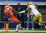 Clemson wide receiver Tee Higgins (5) comes down with control of the ball that was tipped by Notre Dame cornerback Donte Vaughn (8) in the end zone for a touchdown late in the first half of the NCAA Cotton Bowl semi-final playoff football game, Saturday, Dec. 29, 2018, in Arlington, Texas. (AP Photo/Michael Ainsworth)