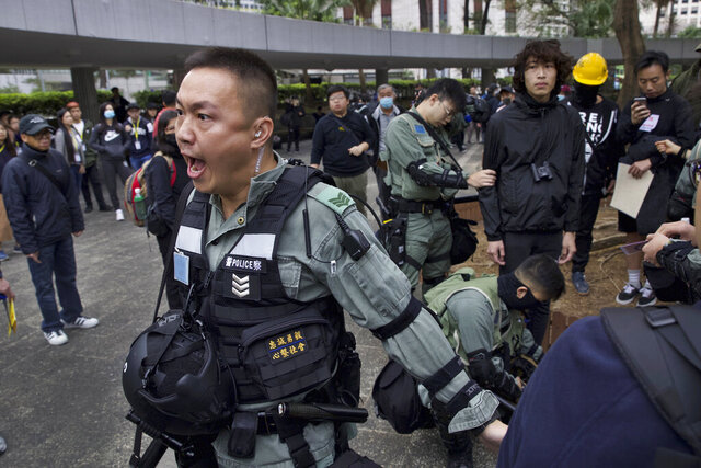 Riot police perform body search on a man ahead of a rally demanding electoral democracy and call for boycott of the Chinese Communist Party and all businesses seen to support it in Hong Kong, Sunday, Jan. 19, 2020. Hong Kong has been wracked by often violent anti-government protests since June, although they have diminished considerably in scale following a landslide win by opposition candidates in races for district councilors late last year. (AP Photo/Ng Han Guan)