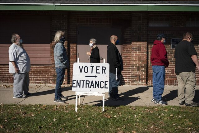 """In this Nov. 3, 2020, photo, voters wait in line outside a polling center on Election Day, in Kenosha, Wis. President-elect Joe Biden shored up the Democrats' """"blue wall,"""" — more sturdily in Michigan, more tenuously in Pennsylvania and Wisconsin — to rebuild the party's path back to the White House. (AP Photo/Wong Maye-E, File)"""
