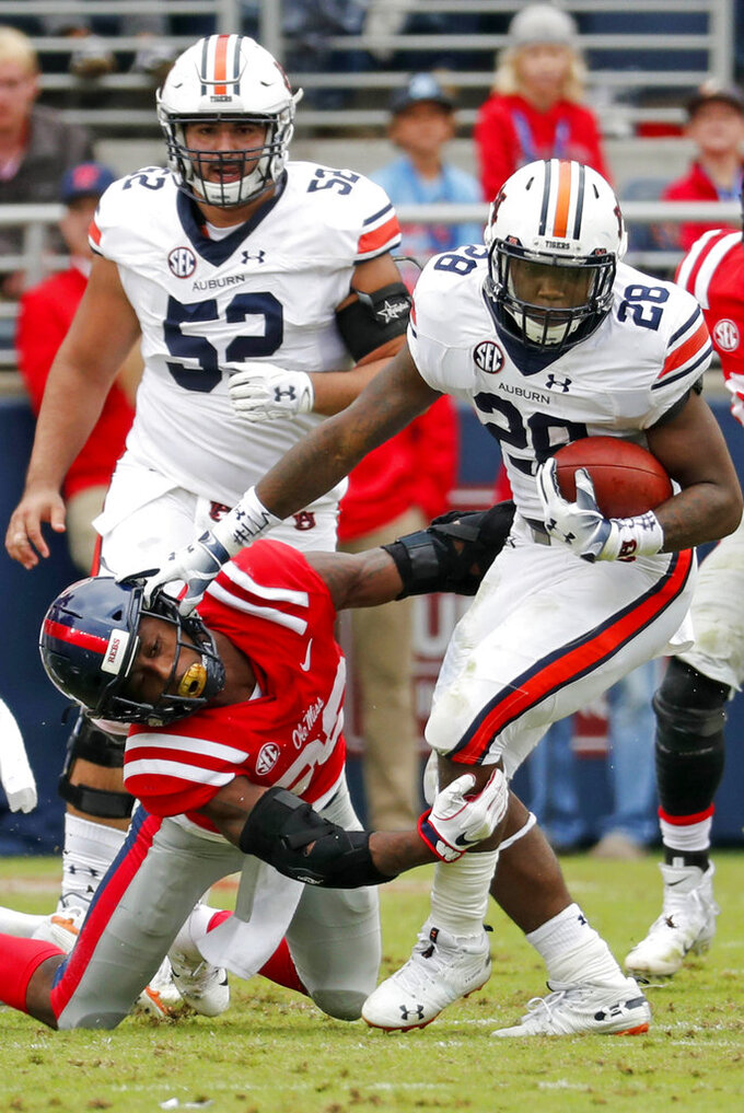 Auburn running back JaTarvious Whitlow (28) pulls away from an attempted tackle by a Mississippi player during the first half of an NCAA college football game on Saturday, Oct. 20, 2018, in Oxford, Miss. (AP Photo/Rogelio V. Solis)