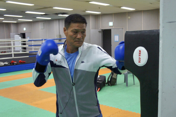 Former Olympic gold medalist Park Si-hun wearing boxing gloves punches a bag for photos after an interview on Jeju Island, South Korea, Tuesday, July 21, 2020. The last South Korean boxer to win an Olympic gold has spent the past 32 years wishing it was a silver. Park's 3-2 decision win over Roy Jones Jr. in the light-middleweight final at the 1988 Seoul Olympics remains one of the controversial moments in boxing history. Jones had seemed to dominate. (AP Photo/Kim Tong-hyung)