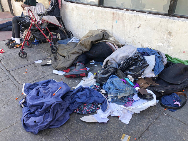FILE - In this July 25, 2019, file photo, sleeping people, discarded clothes and used needles are seen on a street in the Tenderloin neighborhood in San Francisco. A center for people experiencing methamphetamine-induced psychosis will open in San Francisco as the city struggles with a rise in drug overdoses and rampant street drug use. The San Francisco Chronicle reports the center will open in late spring.  (AP Photo/Janie Har, File)