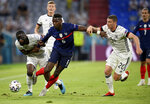 Germany's Antonio Ruediger, left, and Germany's Robin Gosens, right, challenge France's Paul Pogba during the Euro 2020 soccer championship group F match between France and Germany at the Allianz Arena stadium in Munich, Tuesday, June 15, 2021. (Matthias Hangst/Pool via AP)