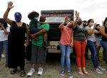People raise their hands during a moment of prayer at a vigil for Army soldier Vanessa Guillén on Sunday, July 5, 2020, in Houston. Army investigators have identified the body of a soldier who vanished more than two months ago from a base in Texas, according to a lawyer for the soldier's family. Remains found last week buried near Fort Hood belong to Guillén and Army officials informed her family in Houston Sunday, attorney Natalie Khawam told The Associated Press. (Godofredo A. Vásquez/Houston Chronicle via AP)