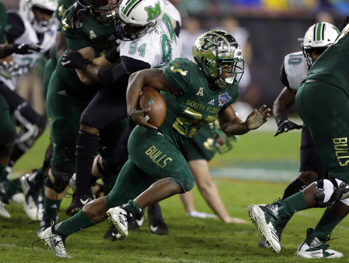 South Florida running back Johnny Ford (20) runs through a hole in the Marshall defense during the second half of the Gasparilla Bowl NCAA college football game Thursday, Dec. 20, 2018, in Tampa, Fla. (AP Photo/Chris O'Meara)