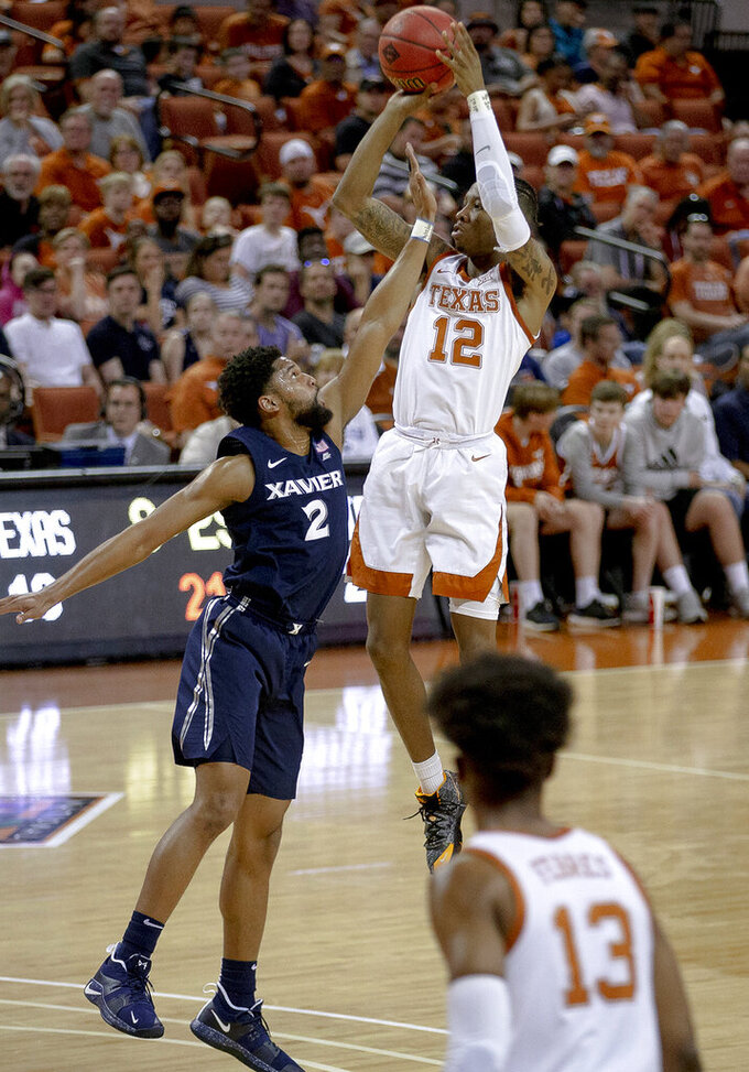 Texas guard Kerwin Roach II (12) shoots over Xavier guard Kyle Castlin (2) during an NCAA college basketball game in the second round of the NIT on Sunday, March 24, 2019, in Austin, Texas. (Nick Wagner/Austin American-Statesman via AP)