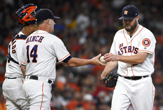 Houston Astros starting pitcher Wade Miley, right, is removed from the game by manager AJ Hinch (14) during the second inning of a baseball game against the Los Angeles Angels, Saturday, Sept. 21, 2019, in Houston. (AP Photo/Eric Christian Smith)