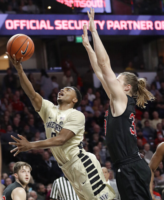 Wake Forest's Brandon Childress (0) drive past North Carolina State's Wyatt Walker (33) during the first half of an NCAA college basketball game in Winston-Salem, N.C., Tuesday, Jan. 15, 2019. (AP Photo/Chuck Burton)