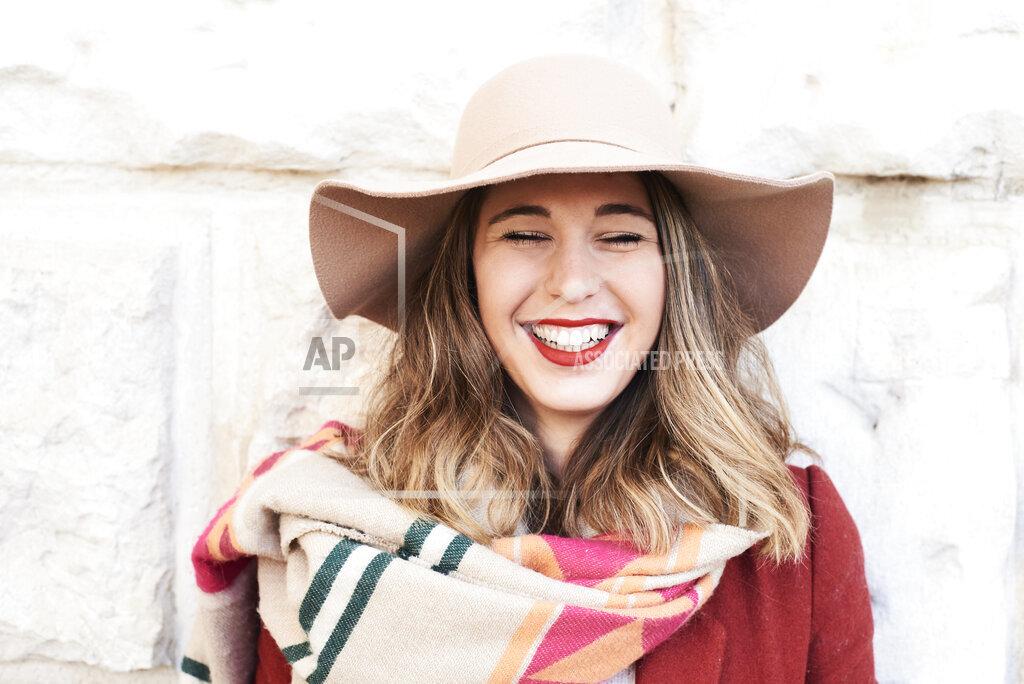 Portrait of a happy stylish woman wearing a floppy hat