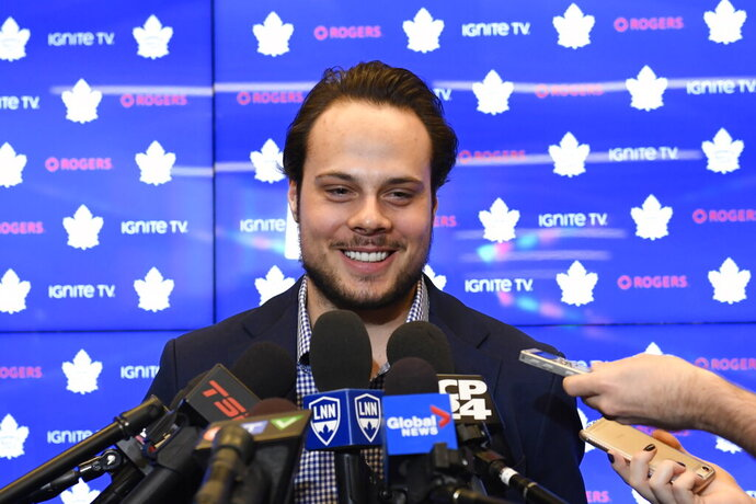 """FILE - In this Tuesday, Feb. 5, 2019 file photo, Toronto Maple Leafs center Auston Matthews smiles at a press conference in Toronto. Auston Matthews could soon wear the """"C"""" as the long-term captain in Toronto. But he also got razzed by his Maple Leafs teammates for doing a stylish GQ fashion photo shoot.  (Nathan Denette/The Canadian Press via AP, File)"""