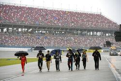 Team members walk through pit row in the rain before a NASCAR Cup series auto race Sunday, Oct. 3, 2021, in Talladega, Ala. (AP Photo/John Amis)