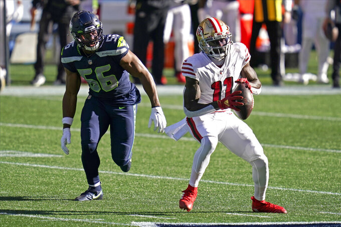 San Francisco 49ers wide receiver Brandon Aiyuk (11) makes a catch in front of Seattle Seahawks linebacker Jordyn Brooks during the first half of an NFL football game, Sunday, Nov. 1, 2020, in Seattle. (AP Photo/Elaine Thompson)
