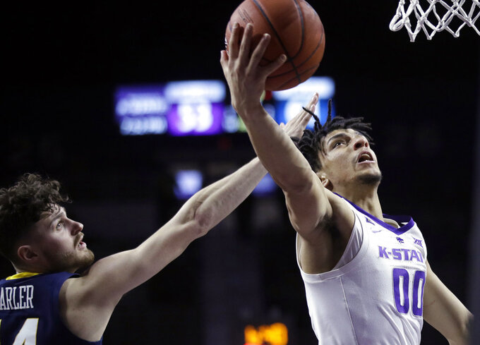 Kansas State guard Mike McGuirl (00) gets past West Virginia guard Chase Harler (14) for a basket during the second half of an NCAA college basketball game in Manhattan, Kan., Wednesday, Jan. 9, 2019. (AP Photo/Orlin Wagner)