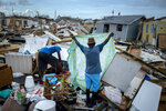 Immigrants from Haiti recover their belongings from the rubble in their destroyed homes, in the aftermath of Hurricane Dorian in Abaco, Bahamas, Monday, Sept. 16, 2019. Dorian hit the northern Bahamas on Sept. 1, with sustained winds of 185 mph (295 kph), unleashing flooding that reached up to 25 feet (8 meters) in some areas. (AP Photo/Ramon Espinosa)