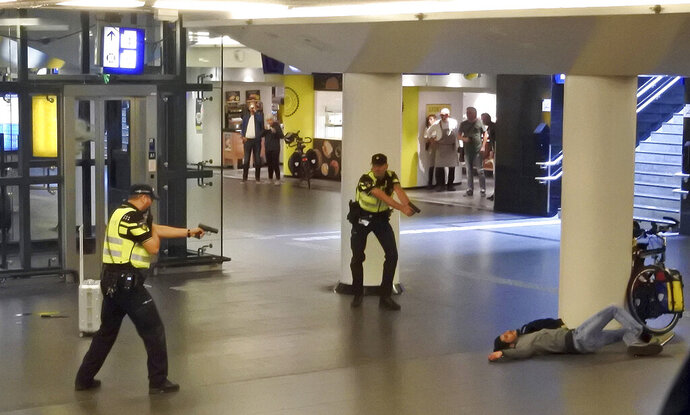 FILE NOT FOR USE IN THE NETHERLANDS - In this Friday Aug. 31, 2018 image, Dutch police officers point their guns at a wounded 19-year-old man who was shot by police after stabbing two people in the central railway station in Amsterdam, the Netherlands. A Dutch court on Monday Oct. 14, 2019, convicted the Afghan asylum-seeker, identified by Dutch authorities as Jawed S, and sentenced him to nearly 27 years imprisonment for stabbing two American tourists in a terror attack at Amsterdam's main railway station. (AP Photo, File)