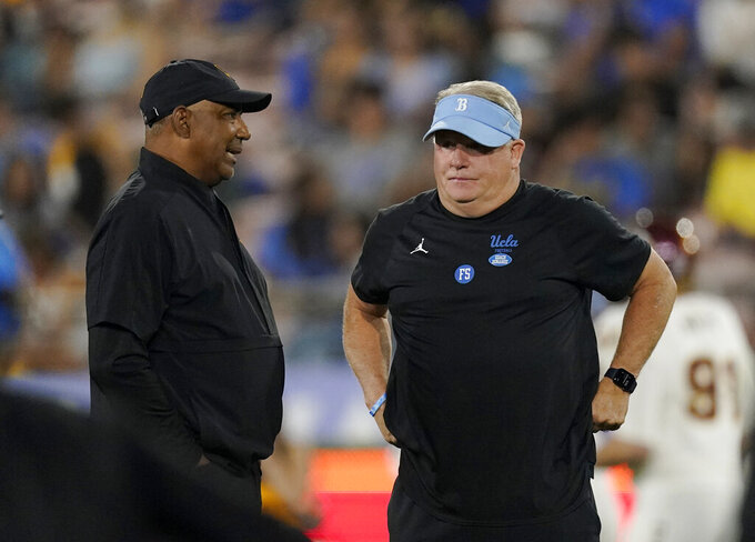 CORRECTS TO ARIZONA STATE DEFENSIVE COACH MARVIN LEWIS NOT HEAD COACH HERM EDWARDS - Arizona State defensive coach Marvin Lewis, left, talks with UCLA head coach Chip Kelly prior to an NCAA college football game Saturday, Oct. 2, 2021, in Pasadena, Calif. (AP Photo/Mark J. Terrill)