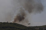 A firefighting plane flies through smoke as fire burns outside the port town of Lavrio, some 60 kilometers (37 miles) south of the Athens, on Thursday July 16, 2020. A children's summer camp and dozens of homes have been evacuated due to a wildfire south of Athens, where high winds hampered an effort to contain the blaze. (AP Photo/Petros Giannakouris)