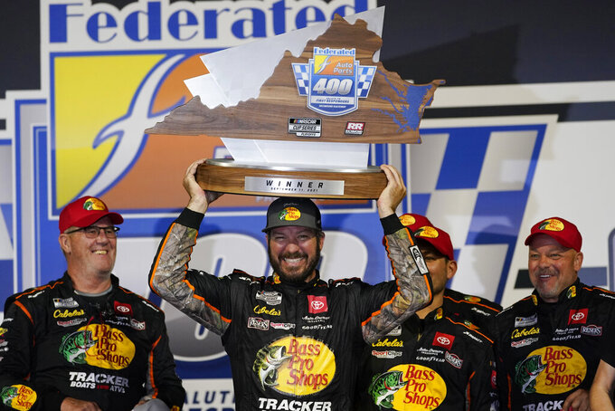 Martin Truex Jr., center, poses with the winners trophy as he celebrates winning the NASCAR Cup series auto race in Richmond, Va., Saturday, Sept. 11, 2021. (AP Photo/Steve Helber)