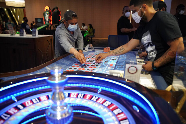 FILE - In this July 4, 2020, file photo, people wear face masks as a precaution against the coronavirus as they play roulette on the Fourth of July at the Strat hotel-casino in Las Vegas. Casinos in Nevada reported sluggish results in house winnings last month, resulting from a slow return of business following more than two months of coronavirus closures. (AP Photo/John Locher, File)