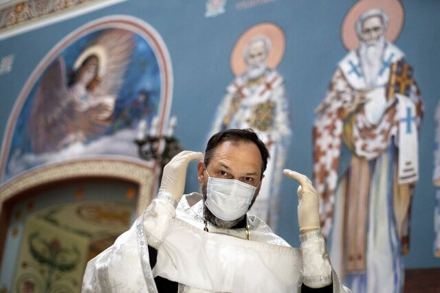 In this photo taken on Tuesday, June 2, 2020, Father Vasily Gelevan, wearing a face mask and gloves to protect against the coronavirus, prepares to conduct a service at the Church of the Annunciation of the Holy Virgin in Sokolniki in Moscow, Russia. In addition to his regular duties as a Russian Orthodox priest, Father Vasily visits people infected with COVID-19 at their homes and hospitals. (AP Photo/Alexander Zemlianichenko)