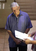 In this Dec. 5, 2018, photo released by the Bureau of Immigration Public Information Office, American Roman Catholic priest Rev. Kenneth Bernard Hendricks looks at documents after being arrested in a church in Naval town in the island province of Biliran, central Philippines. Philippine immigration authorities say they have arrested Hendricks accused of sexually assaulting altar boys in a remote central town in a case one official described as