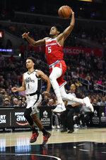 Sacramento Kings guard De'Aaron Fox, right, goes up for a dunk on a breakaway, next to Los Angeles Clippers guard Jerome Robinson during the second half of an NBA basketball game Thursday, Jan. 30, 2020, in Los Angeles. The Kings won 124-103. (AP Photo/Kelvin Kuo)