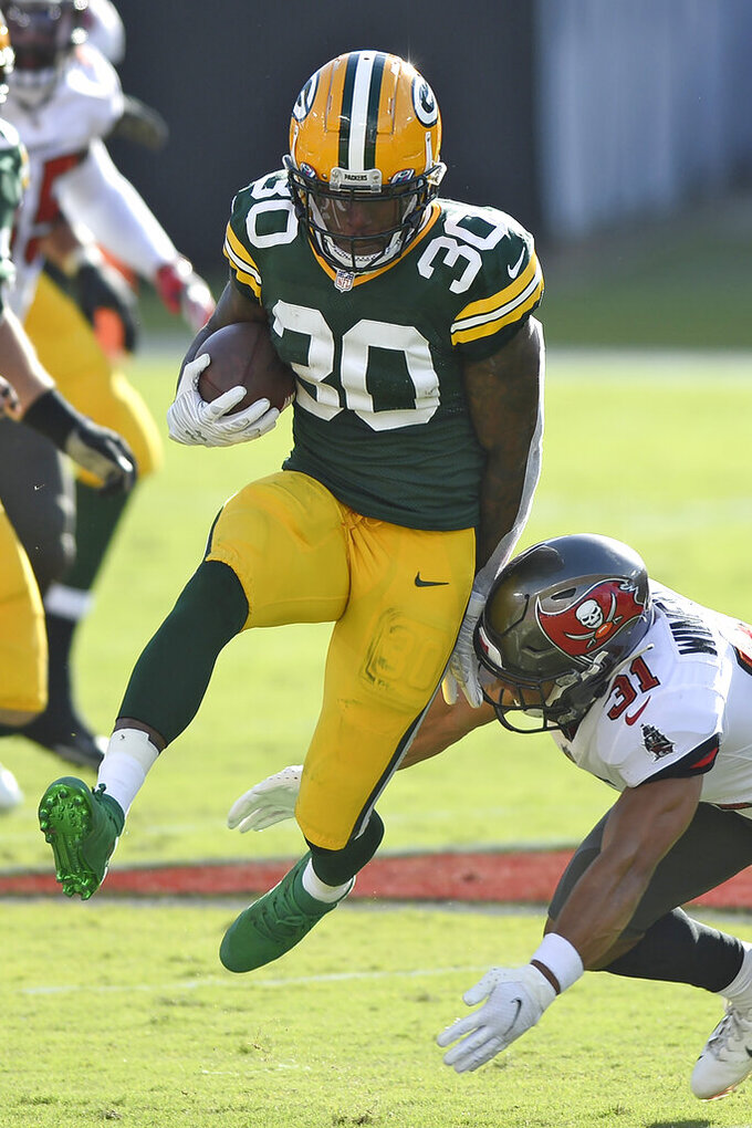 Green Bay Packers running back Jamaal Williams (30) slips a tackle by Tampa Bay Buccaneers strong safety Antoine Winfield Jr. (31) on a run during the first half of an NFL football game Sunday, Oct. 18, 2020, in Tampa, Fla. (AP Photo/Jason Behnken)
