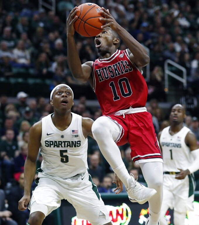 Northern Illinois guard Eugene German (10) makes a layup as Michigan State guard Cassius Winston (5) defends during the first half of an NCAA college basketball game, Saturday, Dec. 29, 2018, in East Lansing, Mich. (AP Photo/Carlos Osorio)