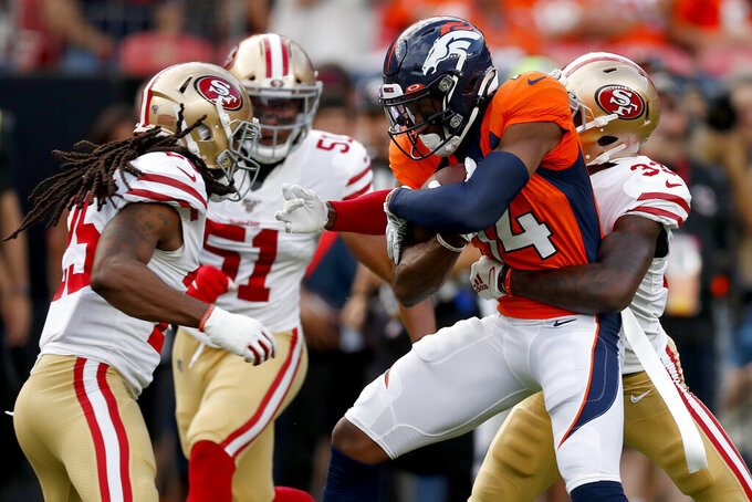 Denver Broncos wide receiver Courtland Sutton (14) runs as San Francisco 49ers defensive back Tarvarius Moore (33) make the tackle and outside linebacker Malcolm Smith (51) and cornerback Richard Sherman (25) defend during an NFL preseason football game, Monday, Aug. 19, 2019, in Denver. (AP Photo/David Zalubowski)