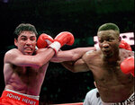 FILE - In this April 12, 1997, file photo, Oscar De La Hoya and Pernell Whitaker, right, exchange punches during their WBC Welterweight Championship fight at Thomas & Mack Center in Las Vegas. Former boxing champion Pernell Whitaker has died after he was hit by a car in Virginia. He was 55. Police in Virginia Beach on Monday say Whitaker was a pedestrian when struck by the car Sunday night, July 14, 2019. The driver remained on the scene, where Whitaker was pronounced dead. (AP Photo/Bob Galbraith, File)