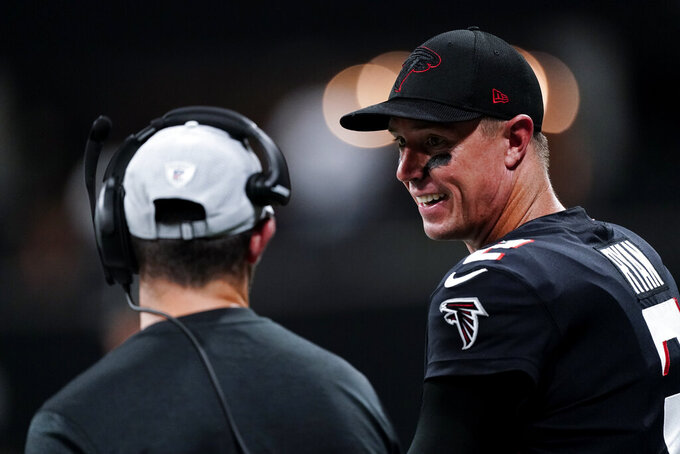 Atlanta Falcons quarterback Matt Ryan, right, stands on the sidelines during the first half of a preseason NFL football game against the Cleveland Browns, Sunday, Aug. 29, 2021, in Atlanta. (AP Photo/John Bazemore)