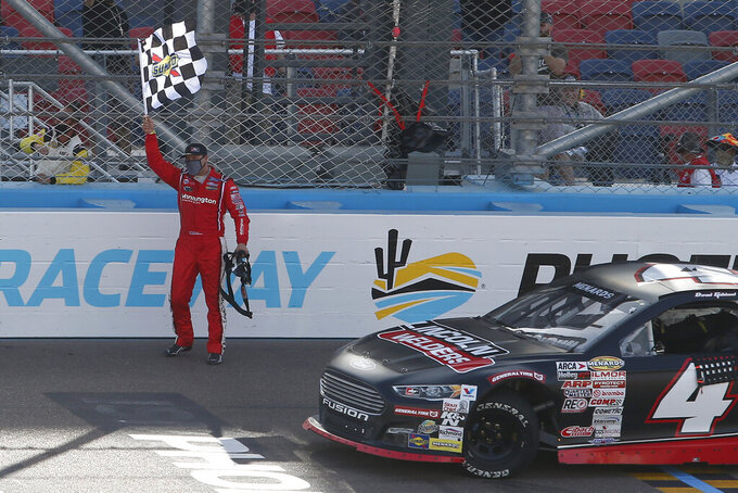 David Gilliland (4) waves the checkered flag after winning an ARCA Series auto race at Phoenix Raceway, Saturday, Nov. 7, 2020, in Avondale, Ariz. (AP Photo/Ralph Freso)