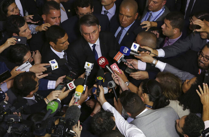 Brazil's President Jair Bolsonaro speaks to the press after signing a second decree that eases gun restrictions, at the Planalto presidential palace in Brasilia, Brazil, Tuesday, May 7, 2019. The decree opens Brazil's market to guns and ammunition made outside of Brazil according to a summary of the decree. Gun owners can now buy between 1,000 -5,000 rounds of ammunition per year depending on their license, up from 50 rounds. Lower-ranking military members can now carry guns after 10 years of service. (AP Photo/Eraldo Peres)