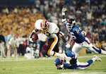 FILE - In this Sept. 11, 1989, file photo, Washington Redskins' Gerald Riggs tries to break free from New York Giants' Greg Jackson, on ground, as Lawrence Taylor, right, moves in to cap the play during an NFL football game in Washington. Second pick became the prototype for the modern linebacker. Taylor revolutionized the sack with his arm chop that stripped the ball. (AP Photo/J. Scott Applewhite, File)