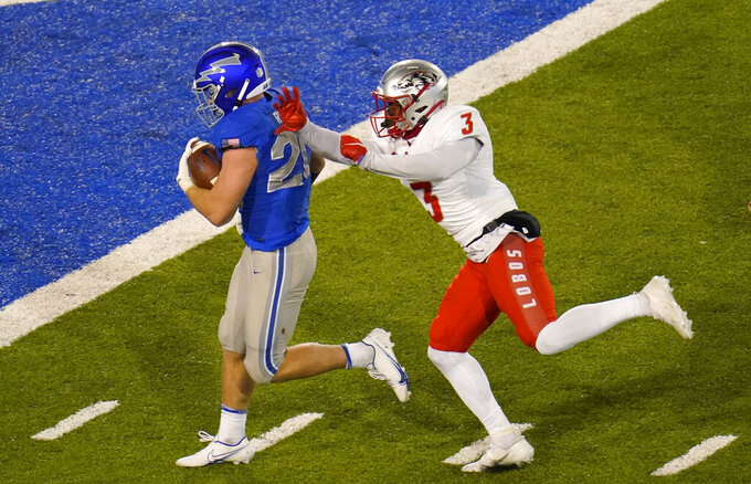 Air Force running back Brad Roberts, left, rambles in for a touchdown past New Mexico safety Patrick Peek during the second half of an NCAA college football game Friday, Nov. 20, 2020, at Air Force Academy, Colo. (AP Photo/David Zalubowski)